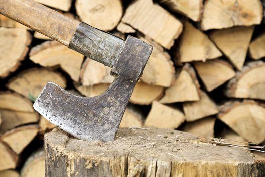 old axe on stump against logs