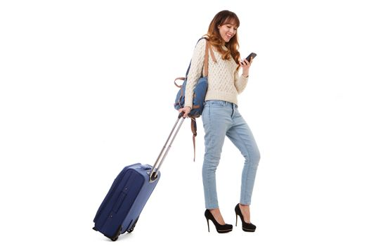 Full body travel woman walking and looking at mobile phone