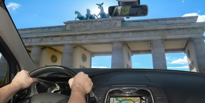 Driving a car towards Brandenburg Gate, iconic landmark in Berlin, Germany