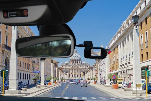 Looking through a dashcam car camera installed on a windshield with view of Via della Conciliazione leading to Saint Peter's Church, Rome, Italy