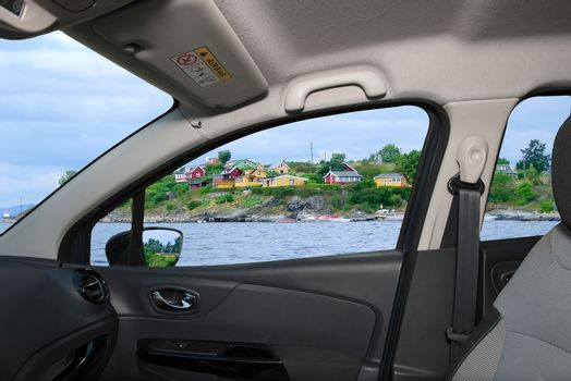 Looking through a car window with view over colorful houses on the shore of Oslo fjord, Oslo, Norway