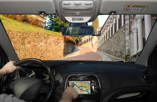 Driving a car while using the touch screen of a GPS navigation system on the slope to the Udine Castle, historical landmark in Udine, Italy