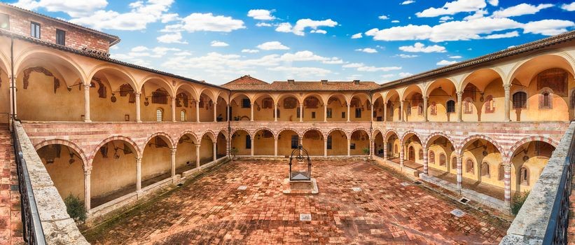 Panoramic view with the scenic courtyard in the friary of the Basilica of Saint Francis, Assisi, Italy. UNESCO World Heritage Site since 2000