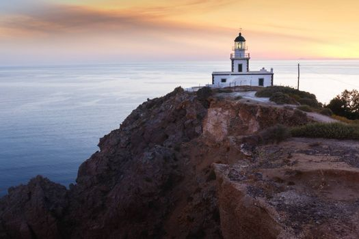 Cliffs and lighthouse in Akrotiri at sunset, Santorini, Greece.
