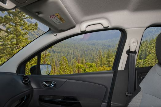 Looking through a car window with view of a beautiful green valley in Yosemite National Park, USA