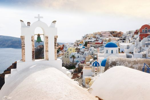 View of sea and Oia village  through traditional Greek white church arch with cross and bells in Oia village of Cyclades Island, Santorini