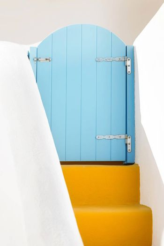 Small blue greek door and yellow steps on Santorini island, Greece