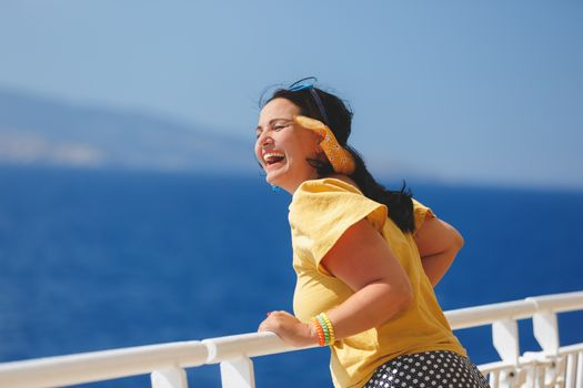 Happy Woman On A Cruise Vacation. standing on deck of cruise ship, strong wind blowing her hair