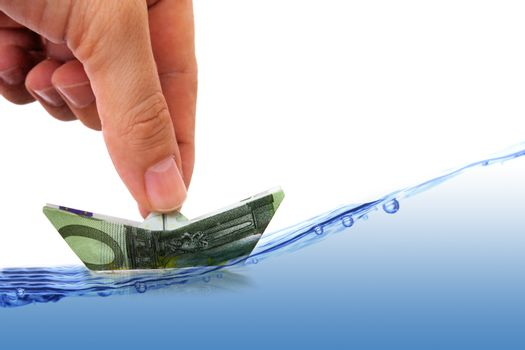 hand with euro banknote as paper boat on wavy waters