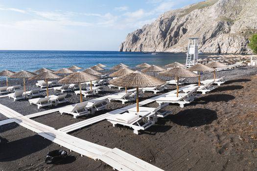 Sunbeds and parasols on blank snd beach. Kamari, Santorini island, Greece
