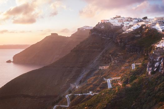 Sunset on the Greek Island of Santorini,with colorful  warm light and clouds over the town. The view follows the edge of the caldera from Thira, Skaros rock,  Imerovigli and Oia towards the sun