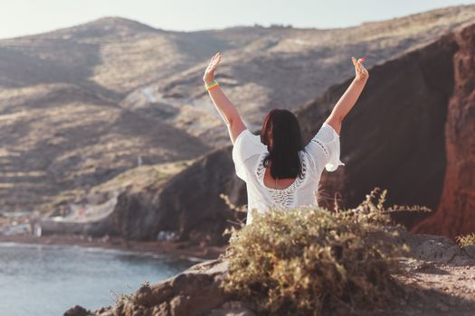 Back view of happy woman on the beach with hands up, sitting on rocks of famous red beach, with volcanic sand  and  rocky shoreline, Santorini, Akrotiri, Greece