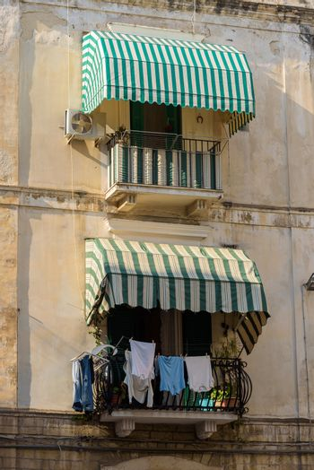 Traditional balconies with awnings and hanging laundry in Bari, Apulia, Italy