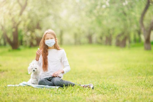 Little girl wearing a protective mask with a dog outdoors because of the coronavirus pandemic