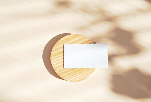 Flat lay of branding identity business name card on wooden and yellow background, light and shadow shape leaves, minimal concept for design