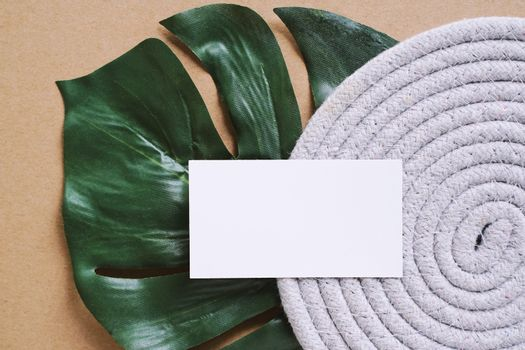 Flat lay of branding identity business name card on green plant leaf background, minimal and organic concept for design