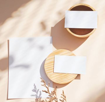 Flat lay of branding identity business name card on yellow background with flower and wooden container, light and shadow shape, minimal concept for design