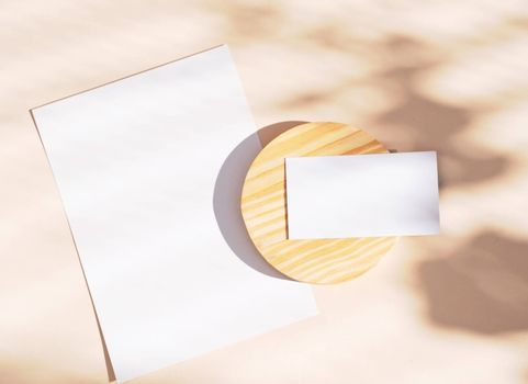 Flat lay of branding identity business name card and blank paper on yellow background, light and shadow shape leaves, minimal concept for design
