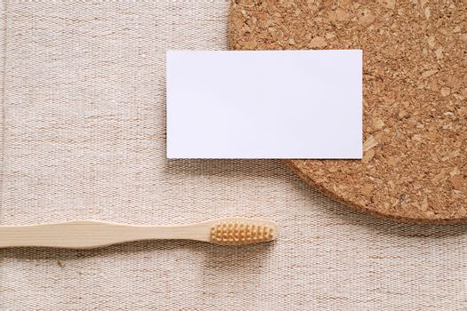 Flat lay branding identity business name card with sustainable products, bamboo toothbrush on fabric background, minimal concept for design