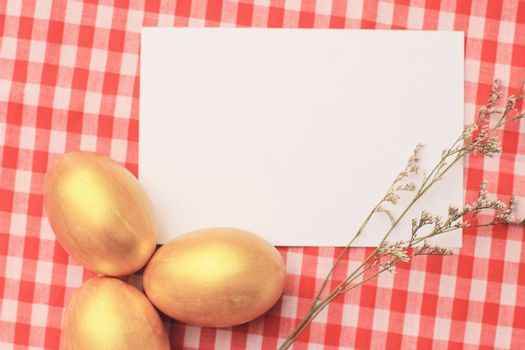 Golden easter eggs on red checkered tablecloth background with blang greeting card, happy easter holiday