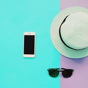Flat lay fashion of smart phone, panama hat and sunglasses on pastel colorful background