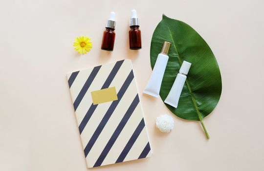 Flat lay of various organic skincare and beauty products for mock up with flower and notebook in minimal style