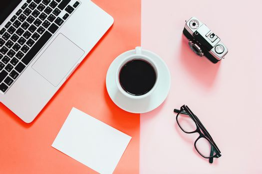 Living Coral color background, Color of the year 2019, flat lay of workspace desk with laptop, blank paper, coffee, eyeglasses and camera