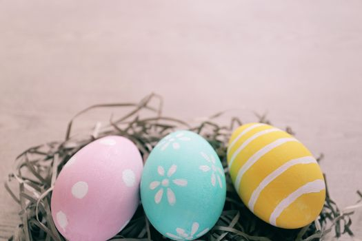 Pastel and colorful easter eggs on nest with wooden background and copy space, happy easter holiday concept