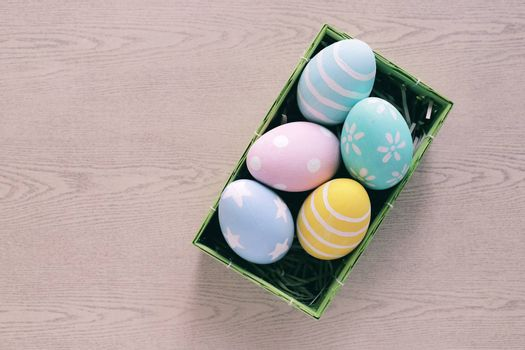 Pastel and colorful easter eggs in nest and basket on wooden background and copy space, happy easter holiday concept