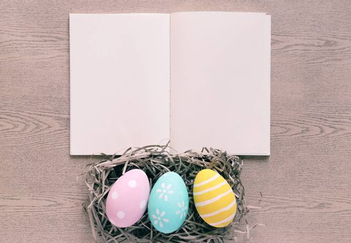 Pastel and colorful easter eggs on nest with blank notebook on wooden background, happy easter holiday concept
