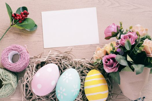Pastel and colorful easter eggs in nest and bouquet of flower with blank card on wooden background, happy easter holiday concept