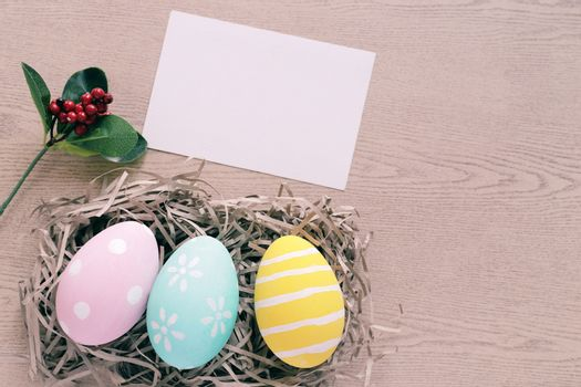 Pastel and colorful easter eggs in nest with blank card on wooden background, happy easter holiday concept