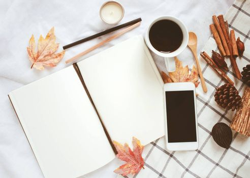 Autumn lifestyle concept, blank notebook, smartphone and coffee with autumn leaves ornaments on white bed sheet background
