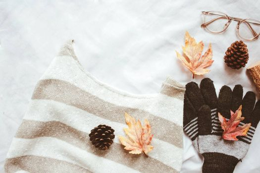 Flat lay of autumn fashion style, sweater, scarf and eyeglasses with maple leaves on white sheet background