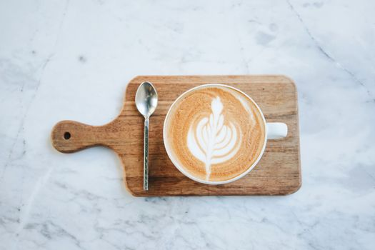 Top view of hot latte coffee on wooden tray on marble table background