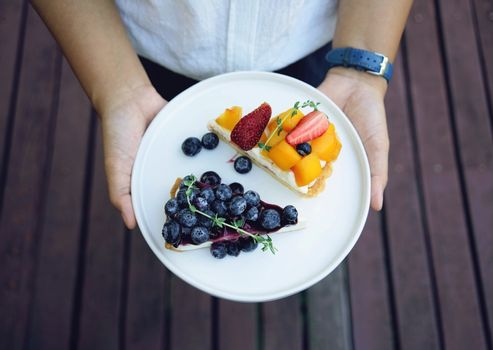 Close up woman hands holding plate of blueberry pie and mango with strawberry tart, homemade bakery style