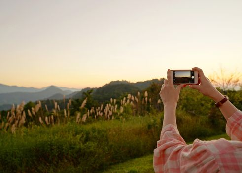 Young asian woman taking a photo with her phone in beautiful mountain view