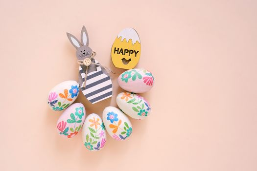 Happy Easter concept with wooden bunny and colorful easter eggs on yellow background. Top view with copy space