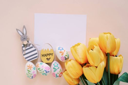 Happy Easter concept with blank card, wooden bunny, colorful easter eggs and yellow tulips. Top view with copy space