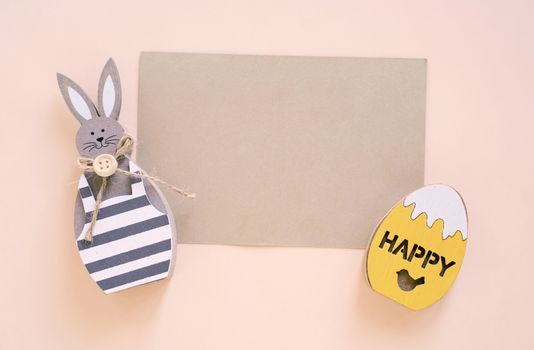 Happy Easter concept with blank card, wooden bunny and colorful easter eggs on yellow background. Top view with copy space