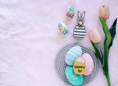 Happy Easter concept with wooden bunny and colorful easter eggs on white fur background and pink tulips. Top view with copy space