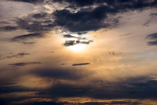 Sunbeams braking through the dark clouds at sunset