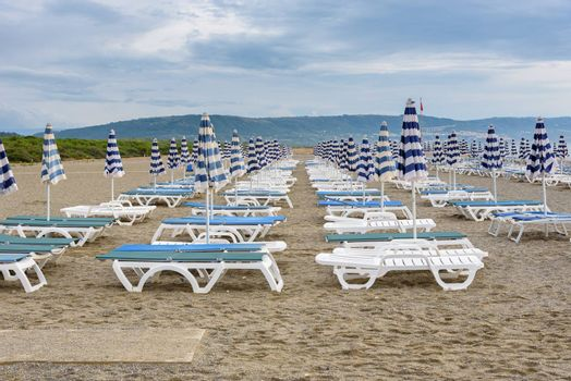 Sunbeds and umbrellas on the calabrian beach on the cloudy evening