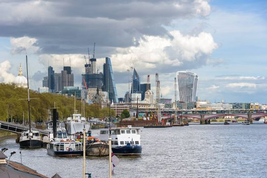 View of ships on Thames River and construction of London city skyscrapers, UK