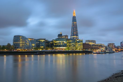 Colorful London skyline over River Thames at dusk on a cloudy day, United Kingdom