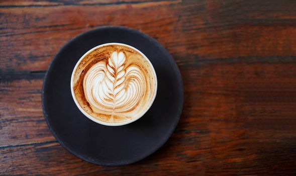 Top view of hot latte or cappuccino coffee on rustic wooden tabletop in the cafe with copy space