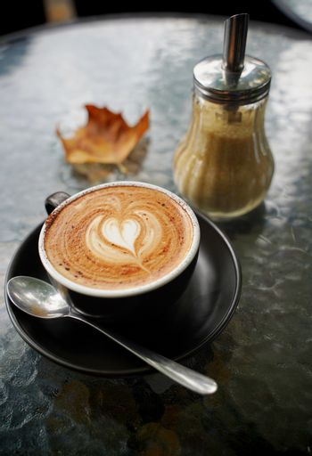Hot cup of coffee latte and flat white with autumn leaves on the table