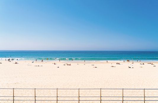 Front view of sea beach with tourist sunbathing, swimming, surfing and relaxing at Bondi beach in Sydney Australia, vacation in summer background