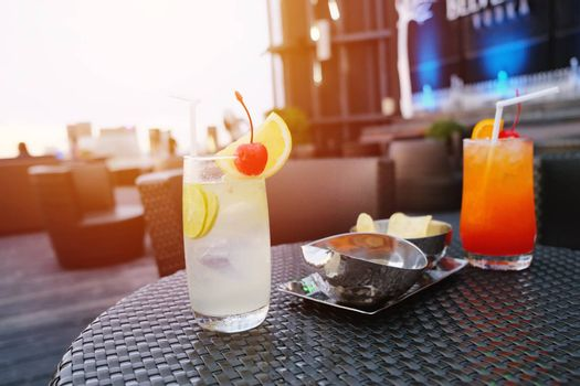Two iced cocktail glasses in rooftop bar for nightlife