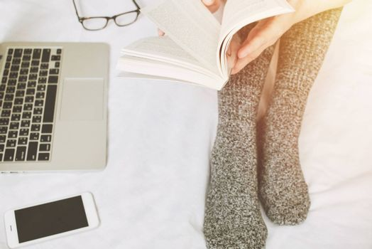 Top view of woman legs in socks reading a book and using laptop on cozy bed, lifestyle concept